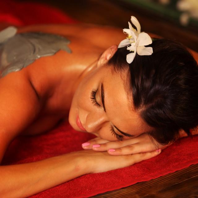 """Mud mask of woman in spa salon. Back massage ."" stock image"