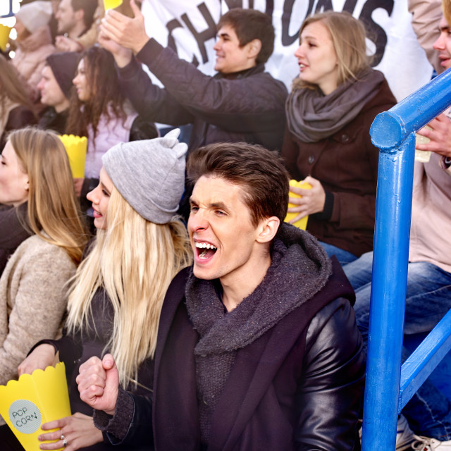 """Fans cheering in stadium and eating popcorn."" stock image"