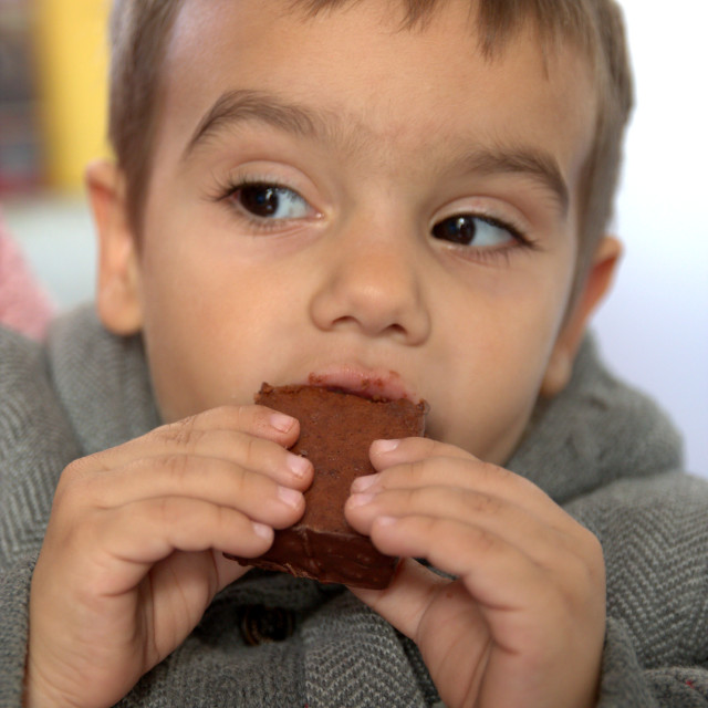 """Boy eating chocolate"" stock image"