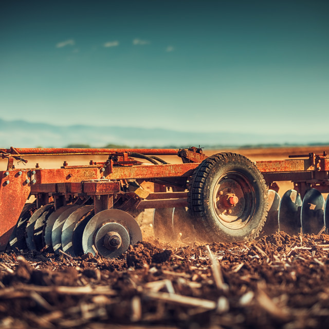 """""""Farmer in tractor preparing land with seedbed cultivator"""" stock image"""