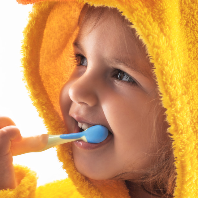"""""""Little baby smiling under a yellow towel and brushing his teeth"""" stock image"""
