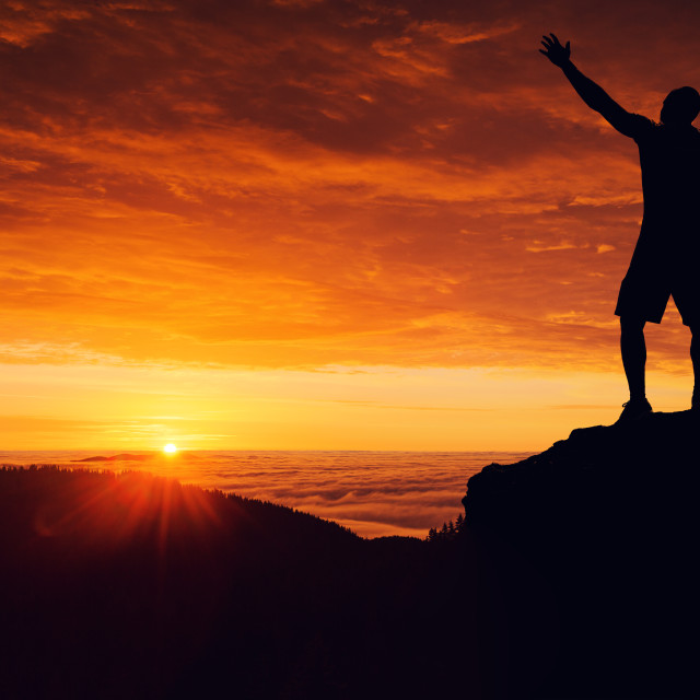 """Man silhouette on the mountain top watching the sunset over clou"" stock image"