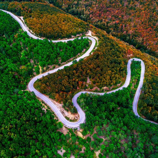 """Aerial view of drone over mountain road and curves going through"" stock image"