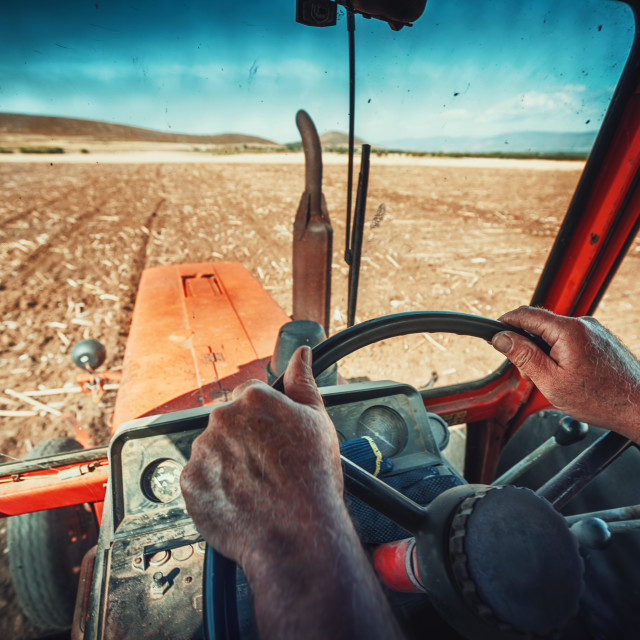 """Closeup hands of farmer, sits inside in the tractor cabin"" stock image"