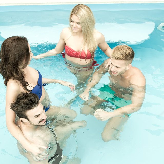 """Friends relaxing together in the pool"" stock image"