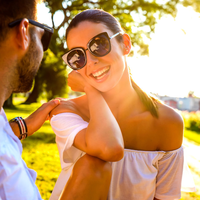 """""""Beautiful young couple relaxing on a sunny summer day on a bench"""" stock image"""