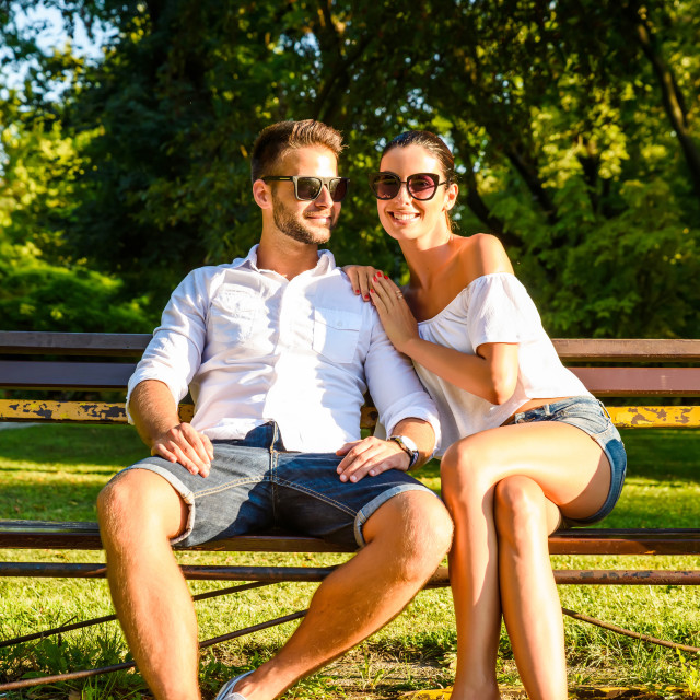 """Beautiful young couple relaxing on a sunny summer day on a bench"" stock image"