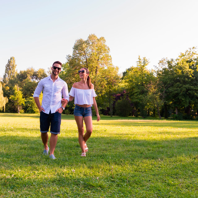 """Beautiful young couple walking together in the park"" stock image"