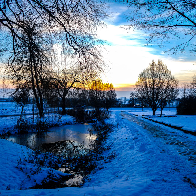 """""""View of a sunset over a winterly landscape"""" stock image"""
