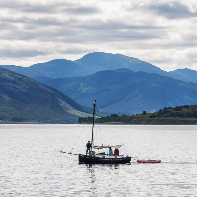 """Ullapool, Scotland - August 15, 2010: People in a small sailing boat in front of the small village of Ullapool in the Highlands in Scotland, United Kingdom"" stock image"