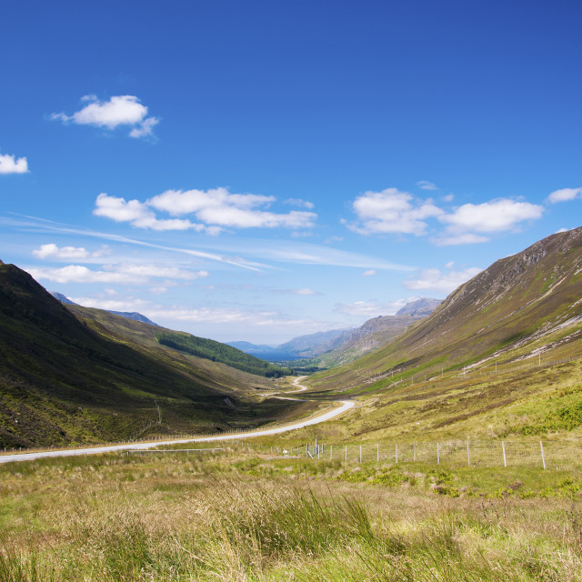 """Scenic winding country road along a valley in the Scottish Highlands, United Kingdom; Concept for travel in Scotland"" stock image"