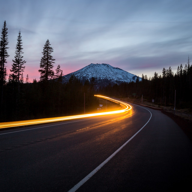 """Car Drives Around Bend at Sunset"" stock image"