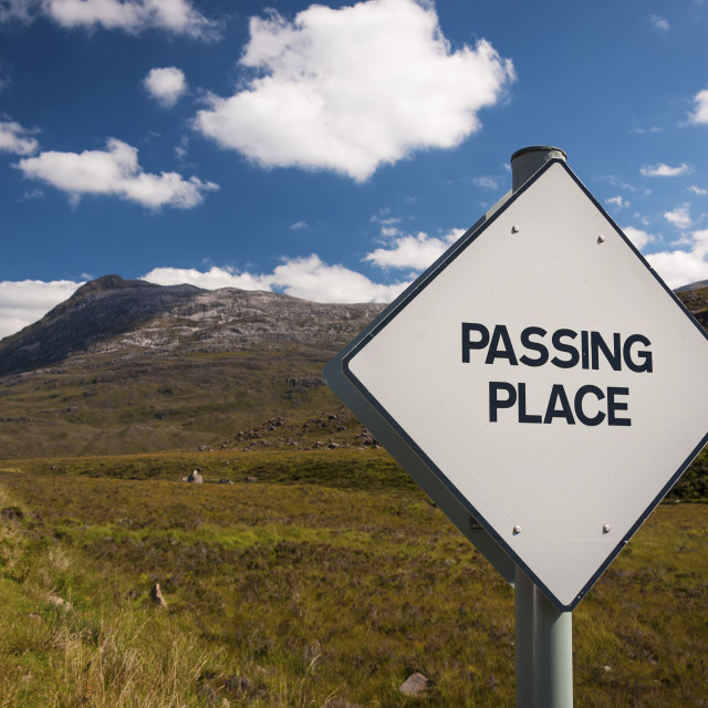 """A Passing Place road sign in a narrow country road in the Highlands of Scotland, United Kingdom; Concept for driving in country roads in the United Kingdom"" stock image"