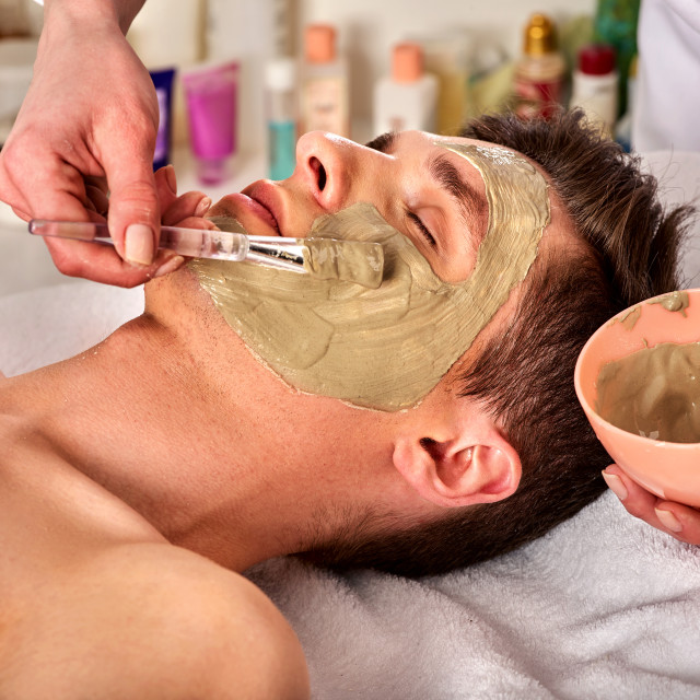 """Mud facial mask of man in spa salon. Face massage ."" stock image"