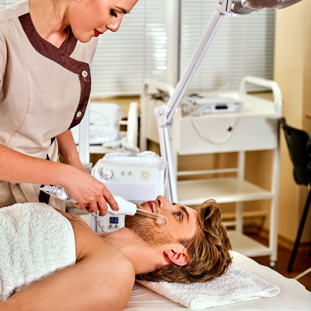 """High frequency machine in spa. Man receiving darsonval facial massage."" stock image"