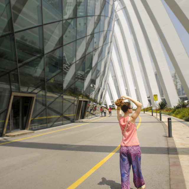 """Woman walking outside Flower Dome, Singapore"" stock image"
