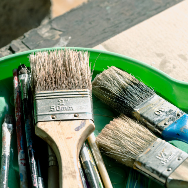 """Old, vintage, used paint brushes in vary sizes in green plastic"" stock image"