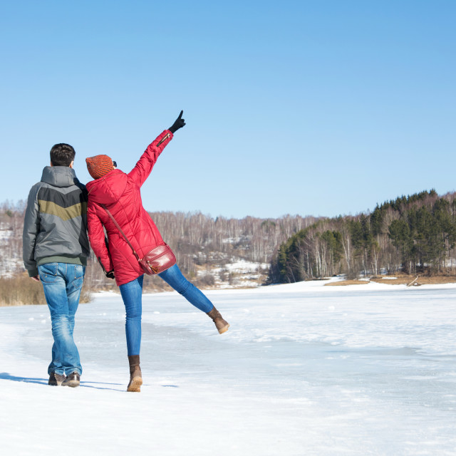 """Couple walking on a frozen lake on a winter day"" stock image"