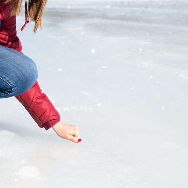 """Girl touching a frozen lake surface"" stock image"