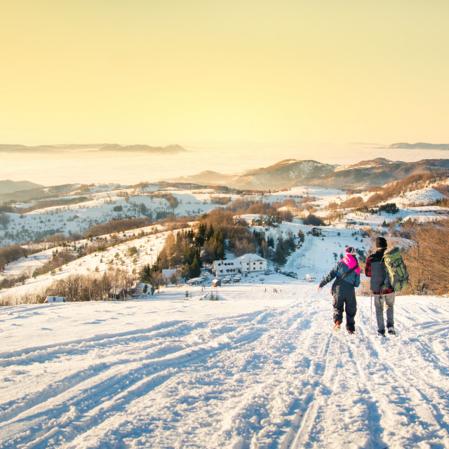 """Couple walking down the snowy mountain in sunset time"" stock image"