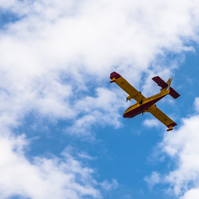 """""""Firefighter aircraft against blue and cloudy sky"""" stock image"""