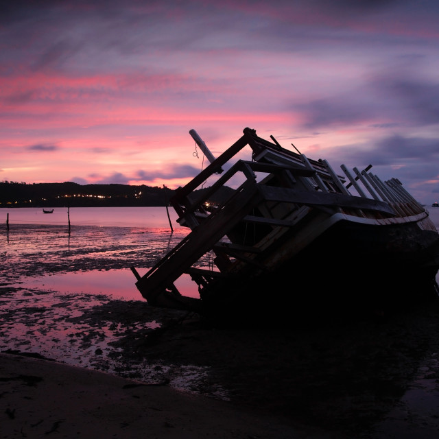 """Wreckship on beach with twilight sky at dusk"" stock image"