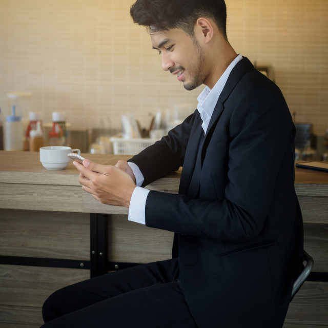 """businessman using smartphone at coffee shop"" stock image"