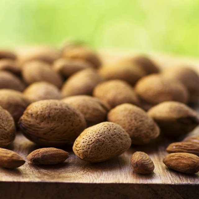 """Almonds on wooden table, green background"" stock image"