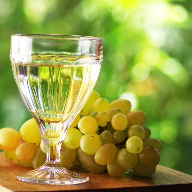 """Close-up of wineglass with white wine on green background"" stock image"