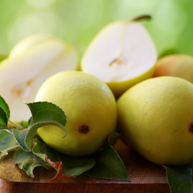 """ripe pears with leaves on wooden table"" stock image"