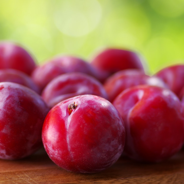"""Sweet red plum isolated on green background"" stock image"