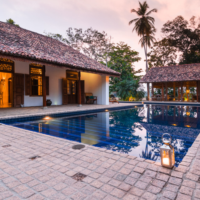 """""""Swimming pool and boutique hotel patio lit by candle lanterns in Tangalle,..."""" stock image"""