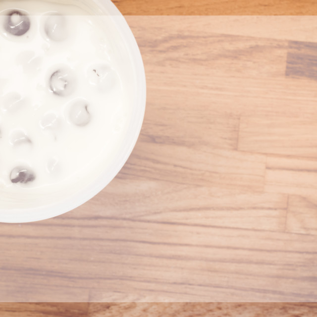 """fruit yogurt container on a wood surface"" stock image"