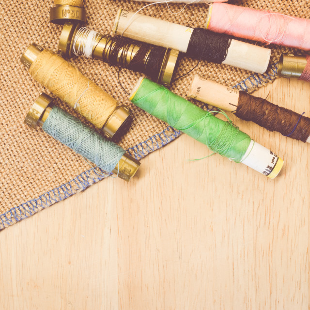 """old sewing thread spools on burlap background"" stock image"