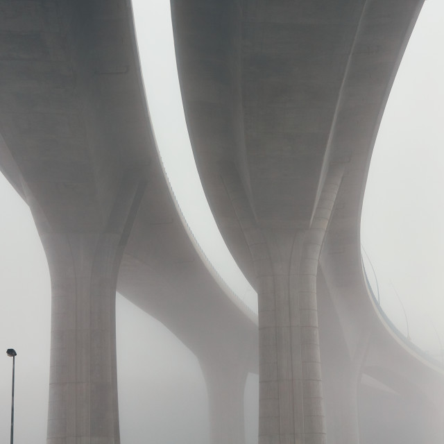 """Pillars of the highway bridge in fog"" stock image"