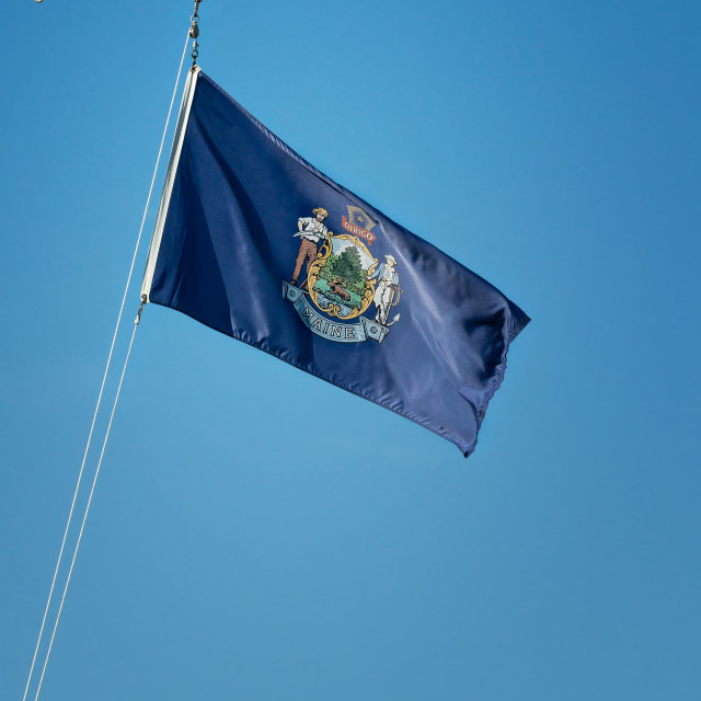 """State flag of Maine against blue sky"" stock image"