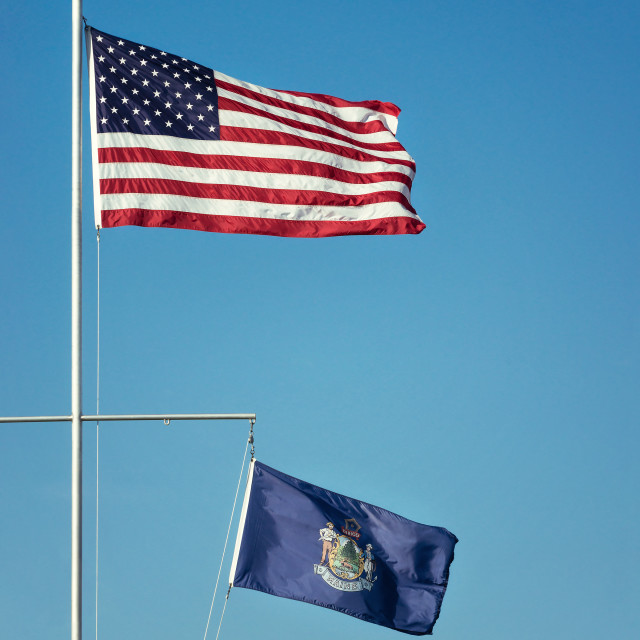 """American flag and the State flag of Maine against blue sky"" stock image"
