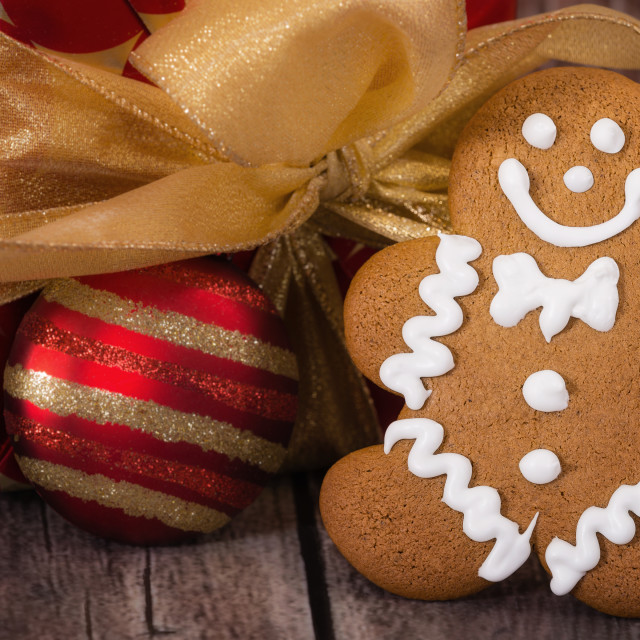"""Gingerbread Men cookie against Christmas present"" stock image"