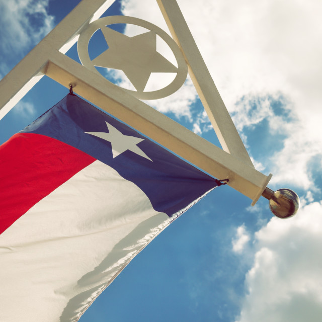 """Texas state flag against blue sky and white clouds"" stock image"