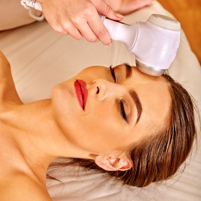 """Young woman receiving electric facial massage."" stock image"