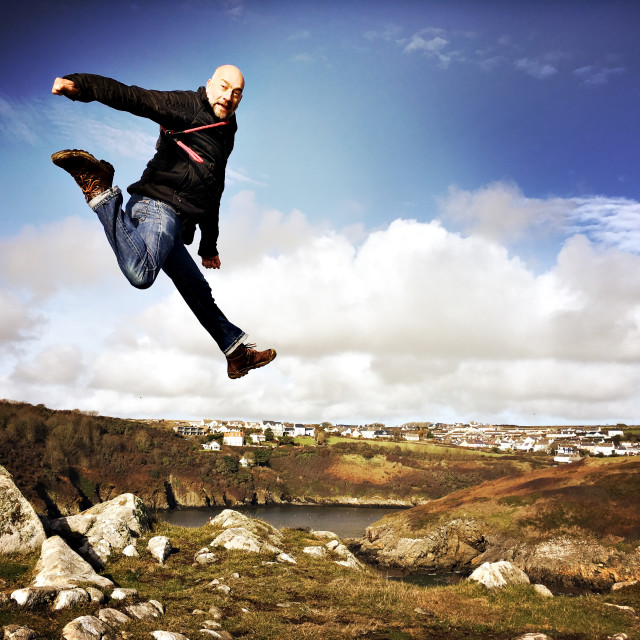 """Man leaps off rocks in Pembrokeshire"" stock image"