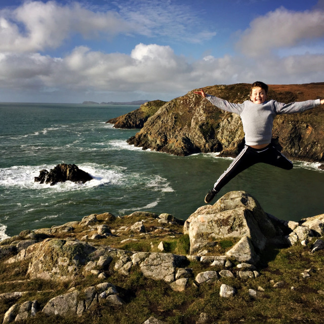 """A boy jumps off a rock at Solva"" stock image"