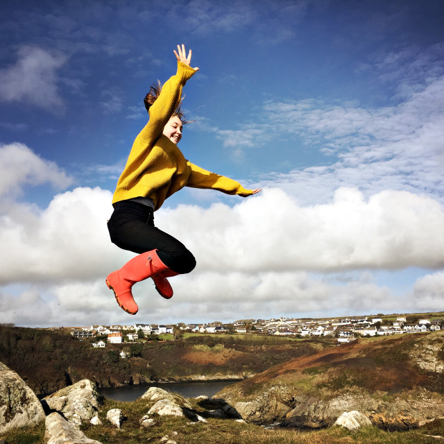 """A teenage girl jumps off a rock in Solva, Wales"" stock image"