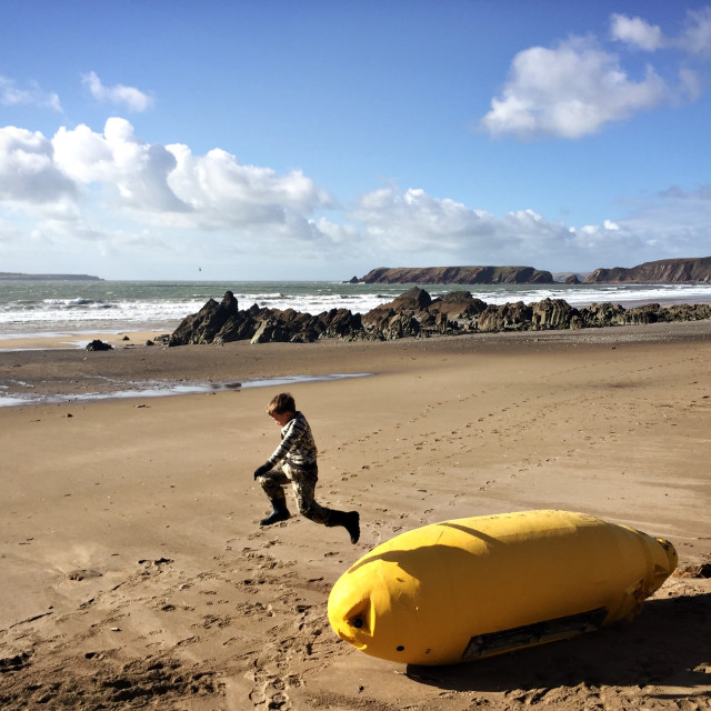 """A boy jumps off a buoy on Marloes Sands beach"" stock image"