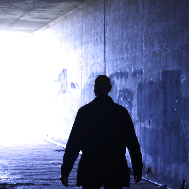 """Silhouette of man stood in a tunnel"" stock image"