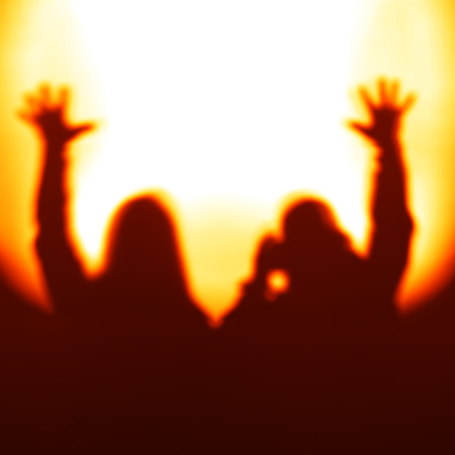 """""""Orange couple silhouettes with hands up in light of floodlight b"""" stock image"""