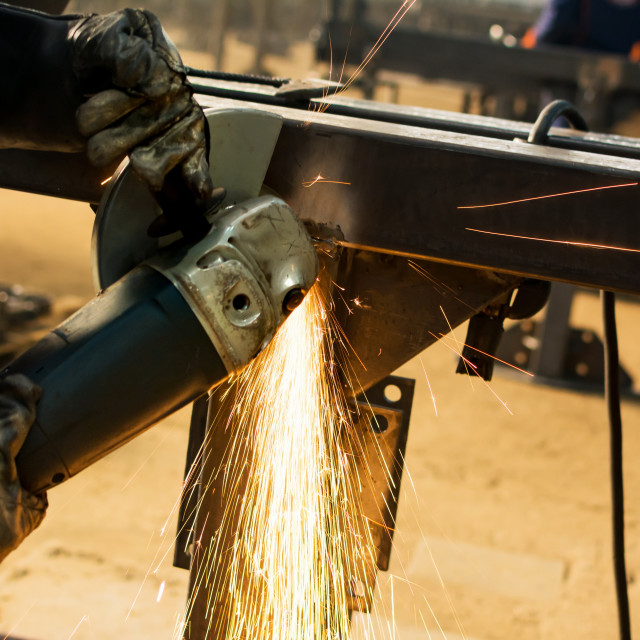 """""""Worker grinding metal with angle grinder"""" stock image"""