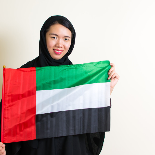 """Muslim woman holding United Arab Emirates flag"" stock image"