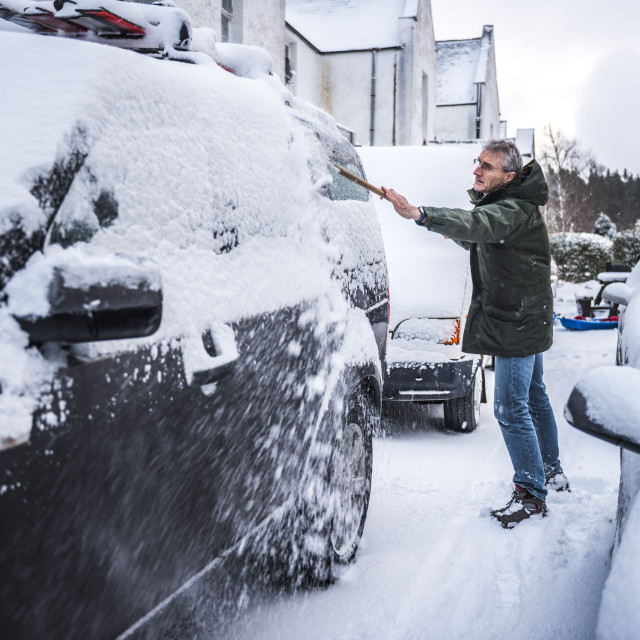 """Removing snow from a car, Cairngorms National Park, Scotland"" stock image"