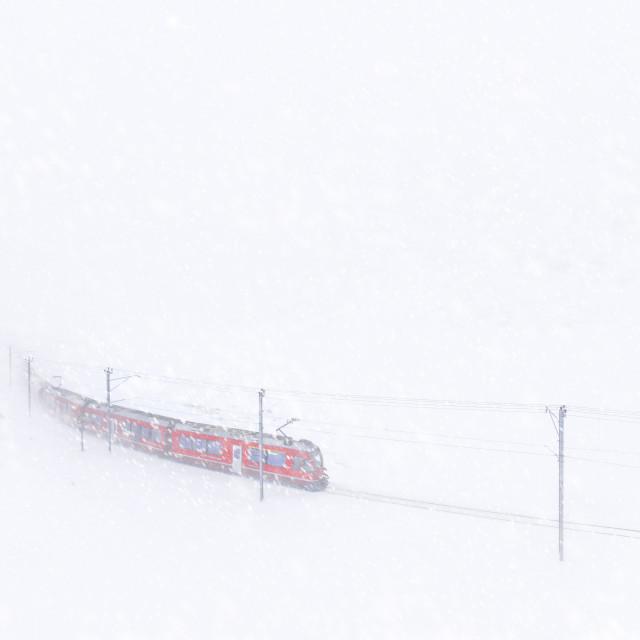 """""""Bernina Express train at Bernina Pass during a snowstorm, canton of..."""" stock image"""